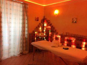 camera con lettino da passaggio e parete di mattoni di sale rosa